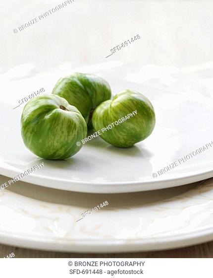 Three Green Heirloom Tomatoes on a White Plate