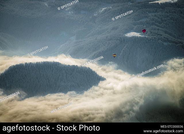 Austria, Salzkammergut, Hot air ballons over forest