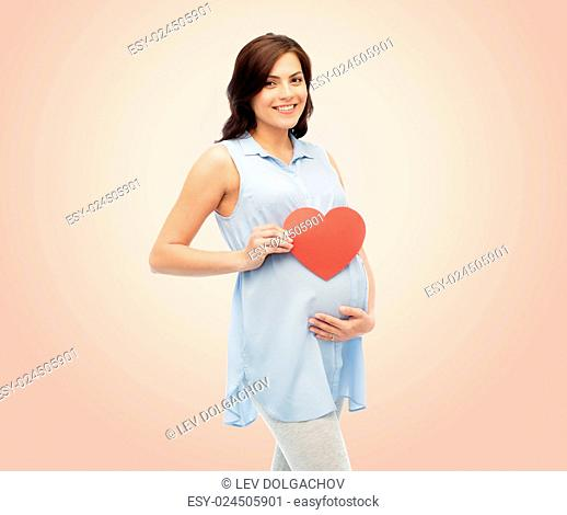 pregnancy, love, people and expectation concept - happy pregnant woman with red heart shape touching her belly over beige background