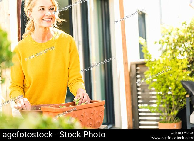 Portrait of smiling mature woman gardening on terrace