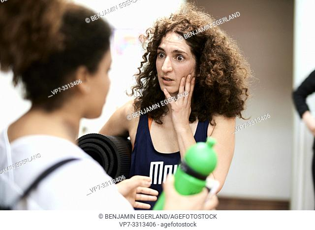 apprehensive woman listening to story of friend in fitness studio