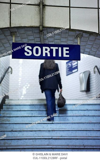 Woman climbing railway station stairs