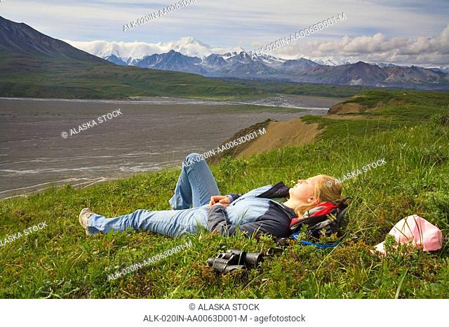 Female day hiker sleeps on the tundra at Grassy Pass near the Eielson Visitor Center Denali National Park Alaska