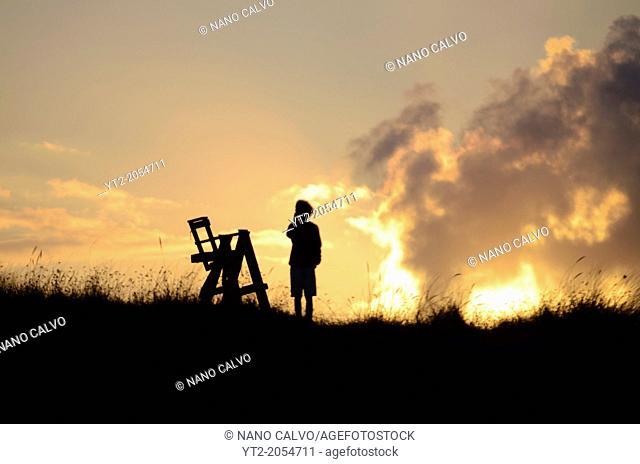 Silhouette of boy and lifeguard chair at sunset on Vega Beach (Playa de Vega), Asturias
