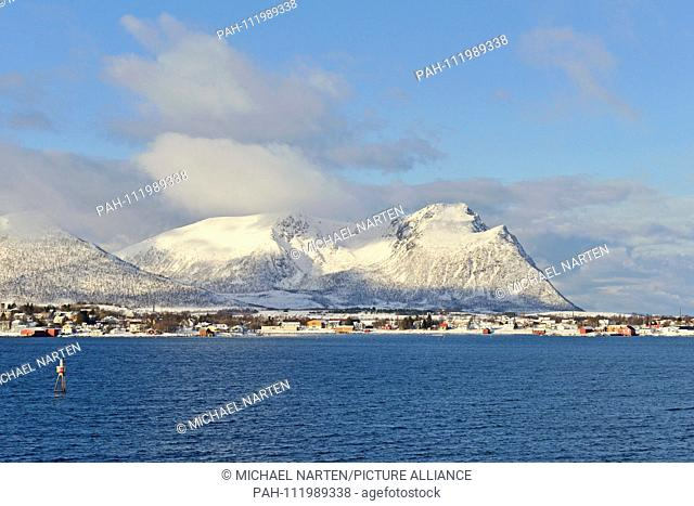 Snowcapped mountains on the Vesterålen Island Andøya with buildings from the small village Risøyhamn at the waterside, 10 March 2017 | usage worldwide