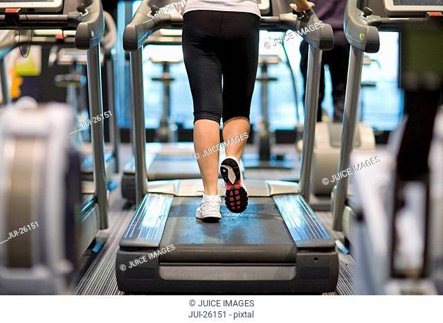 Senior woman walking on treadmill in health club