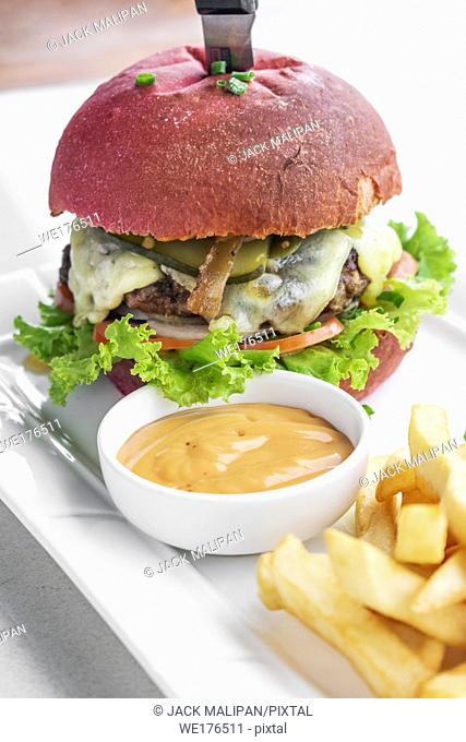 beetroot red bun cheese burger snack set with fries and chilli mayo on white plate