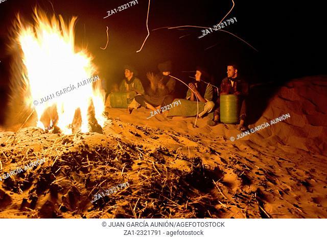 Berber men play drums arround the fire, Zagora, Morocco