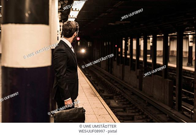 Young businessman waiting at metro station platform
