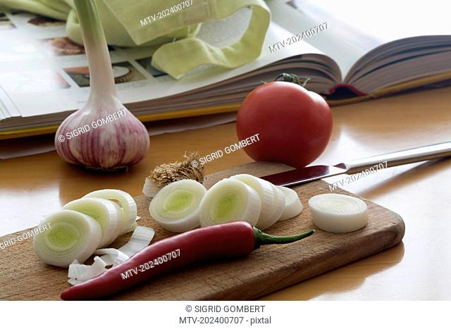 Slices of fennel with chilli and cookery book on the table
