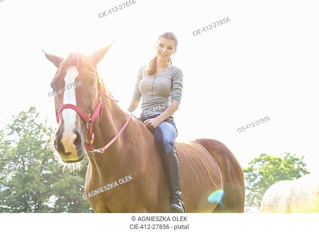 Smiling woman riding horse bareback
