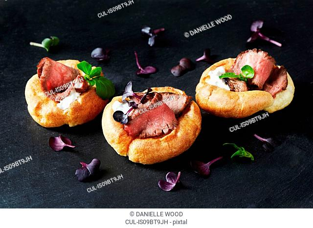 Still life with canapes of roast beef in yorkshire puddings on black slate