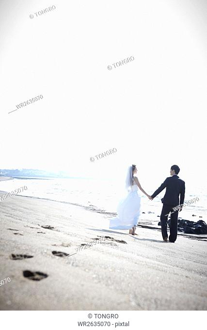 Back of young smiling wedding couple walking holding hands on a beach