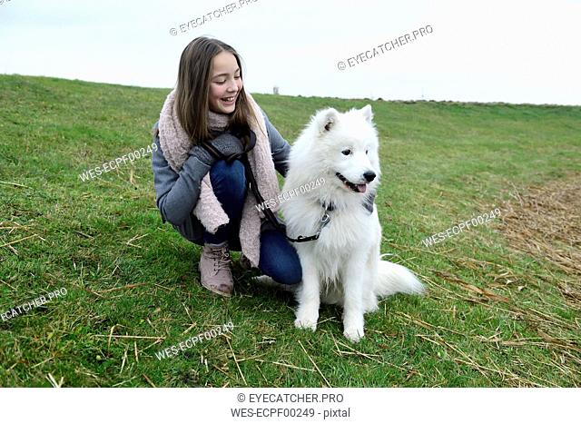 Happy girl crouching on a meadow with her dog