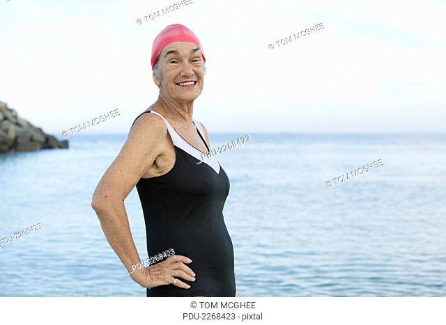 senior women at beach smiling and posing in black swimsuit and red swim cap