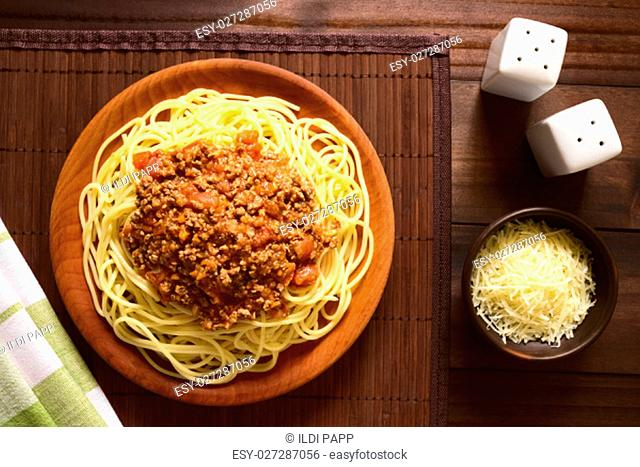 Spaghetti with homemade bolognese sauce made of fresh tomato, mincemeat, onion, garlic and carrot, served on wooden plate with grated cheese on the side
