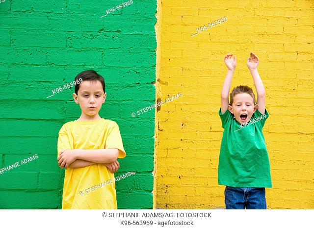 Two boys against colorful yellow and green wall