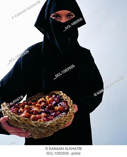 Arab woman holding a basket with dates
