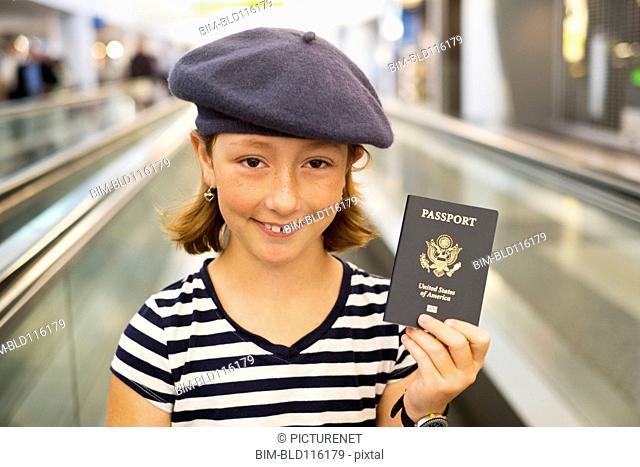 Caucasian girl holding passport in airport
