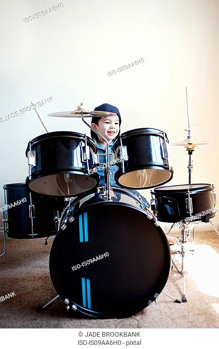 Male toddler playing on drum kit