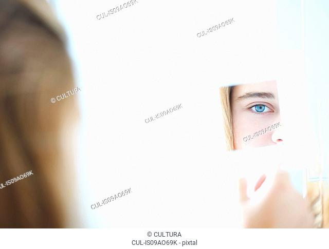 Close up over the shoulder view of teenage girl in hand mirror