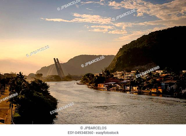 Marapendi Lagoon seen from above with houses on the hill during sunset, golden light. Jet skis are riding on the lake. Barra da Tijuca, Rio de Janeiro