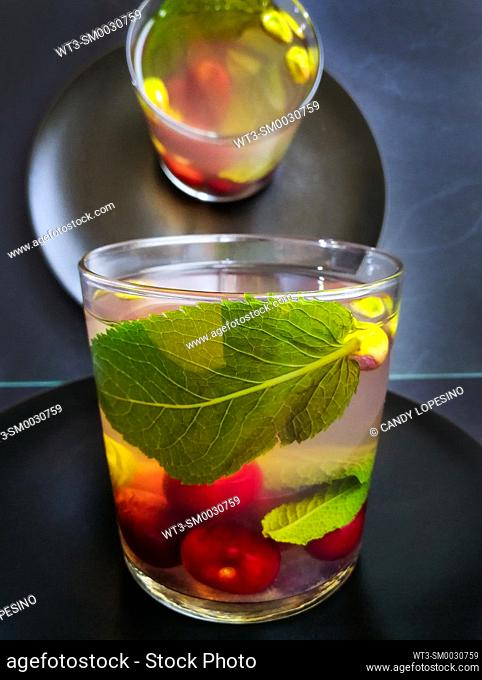 Glass of tea with cherries, pistachios and mint on black plate
