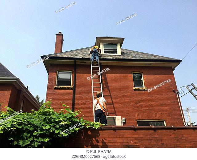 Two men on a ladder working on the slate roof of a red-brick home, Ontario, Canada