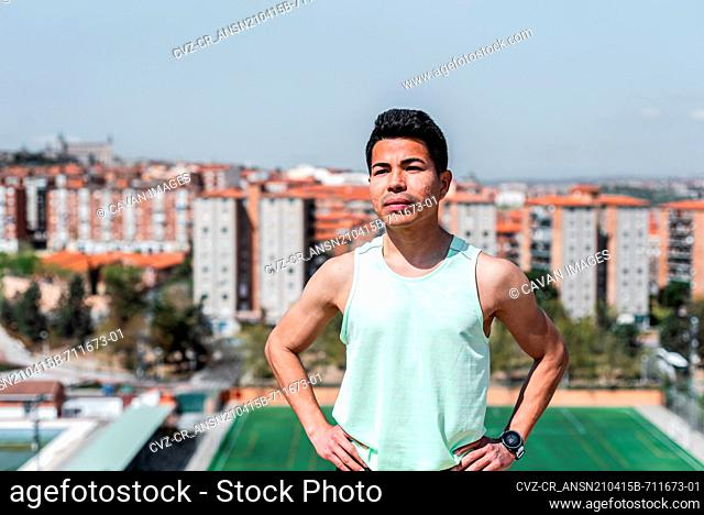 Portrait of Latin American athlete. Background soccer field and residential buildings. Running concept