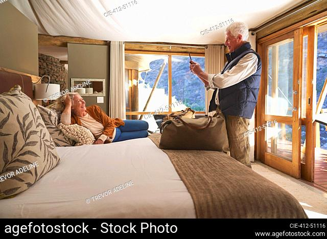 Senior man with camera phone photographing wife on hotel bed