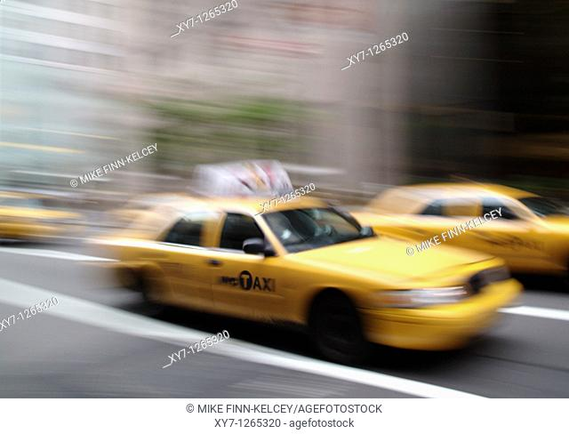 A yellow New York City taxi cab in motion in the United States of America