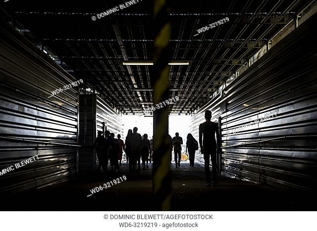 Silhouetted people in a tunnel at the entrance to the Warschauer Strasse SBahn station in Berlin, Germany