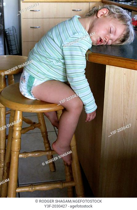 A two-year-old boy, sits up, fast asleep waiting for his supper ..