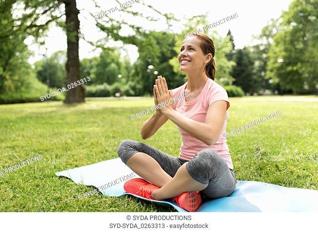 happy woman meditating in summer park
