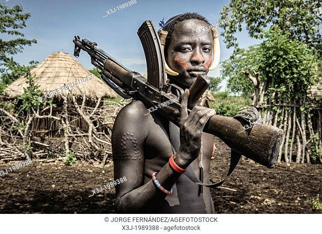 Portrait of a young mursi man holding a kalashnikov, Omo valley, Ethiopia