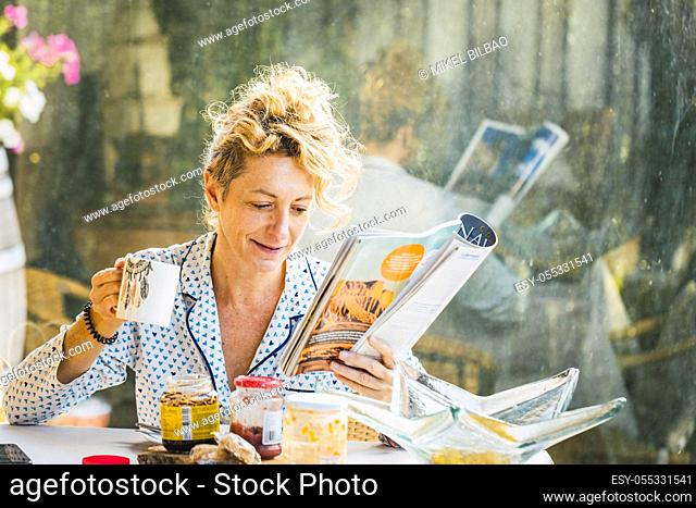 Blonde young mature woman in pyjamas at home in breakfast time, reading a magazine and having a cup of coffee