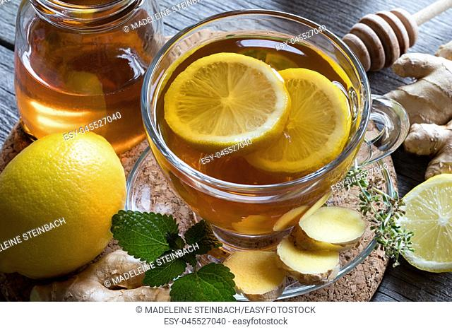 A cup of tea with ginger, lemon, melissa and honey