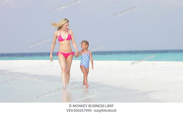 Daughter skips along beach towards camera holding mother's hand.Shot on Canon 5d Mk2 with a frame rate of 30fps