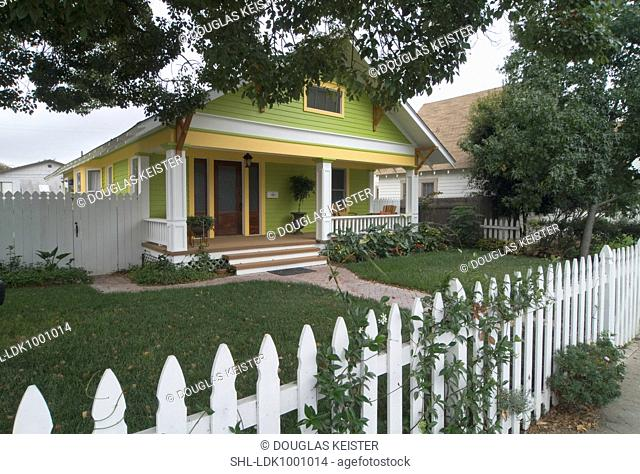 Front exterior of a yellow and green bungalow