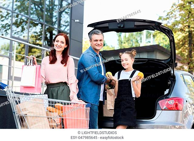 beautiful happy family packing shopping bags in car
