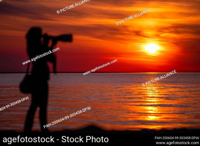 02 June 2020, Mecklenburg-Western Pomerania, Timmendorf (poel): A photographer watches the sunset over the Baltic Sea from the beach on the island of Poel