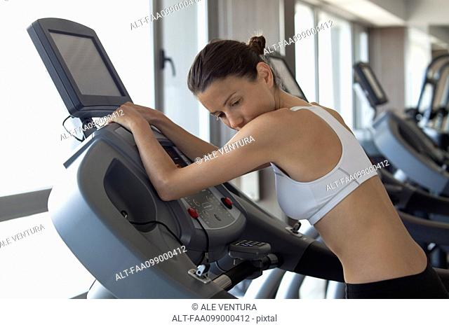 Woman using exercise machine in health club