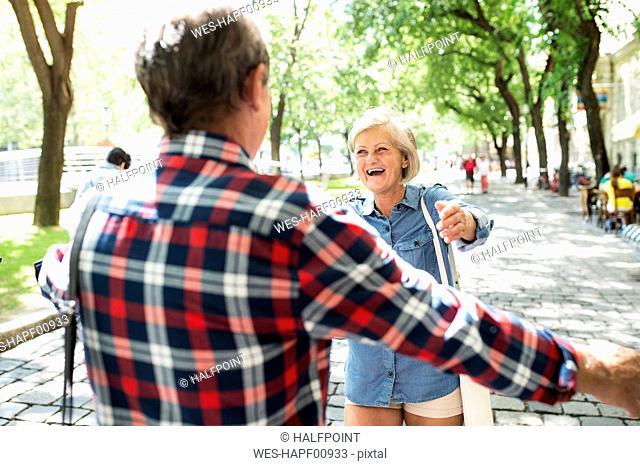 Portrait of happy senior woman greeting senior man