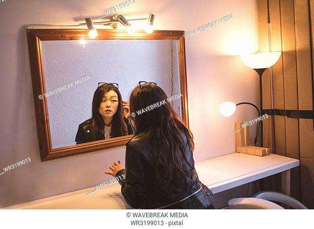Model applying eyeliner in changing room
