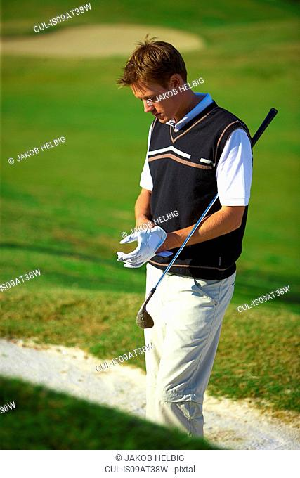 Golfer wearing golf glove carrying golf club under arm, looking down