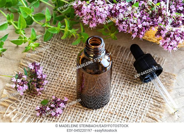 A bottle of essential oil with fresh blooming oregano twigs