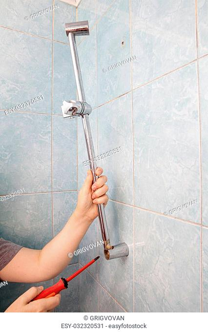 Close-up hands uninstalling the broken vertical height adjustable shower bar slider rail holder, using red phillips screwdriver
