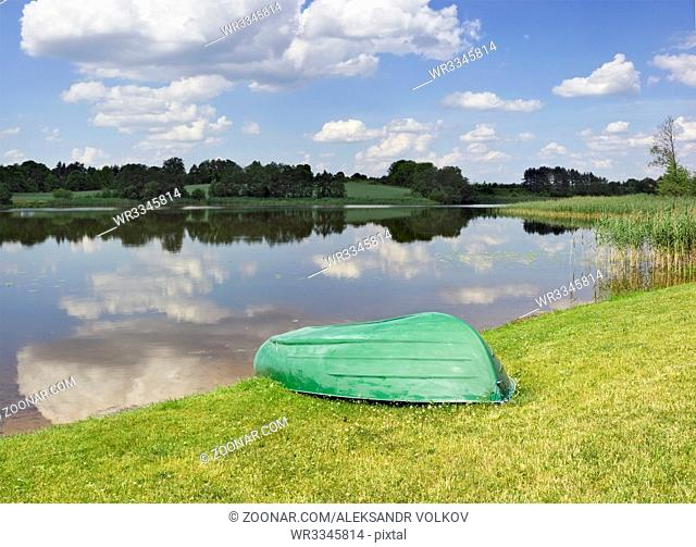 The green boat waits for the travelers ashore. Summer sunny day landscape