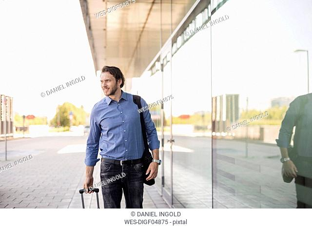 Businessman with rolling suitcase and laptop bag outoors