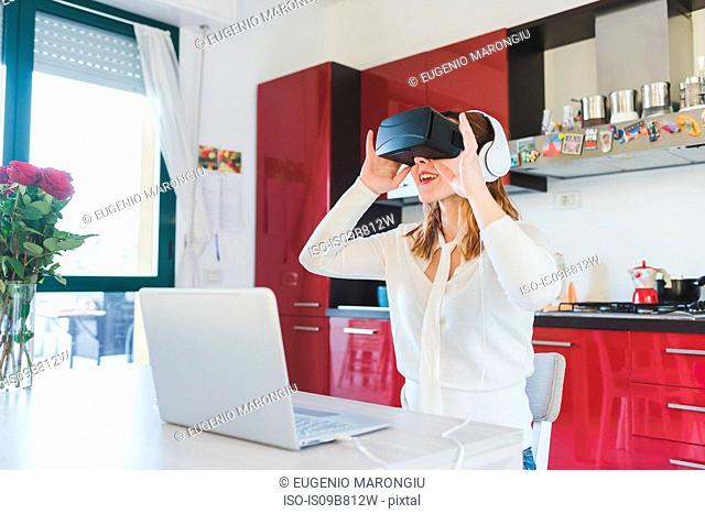 Young woman at kitchen table looking through virtual reality headset